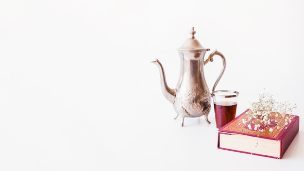 Teapot and book on white