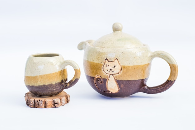 Teapot and ceramic stoneware cup with white background