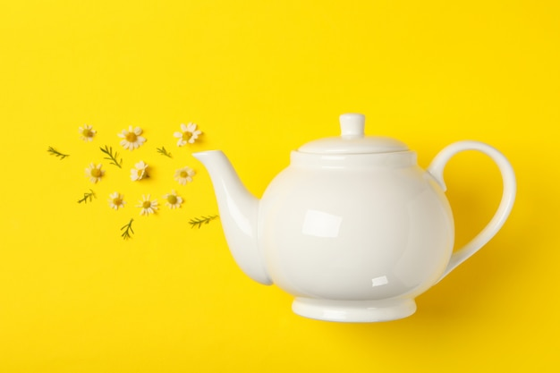 Teapot and chamomiles on yellow. chamomile tea