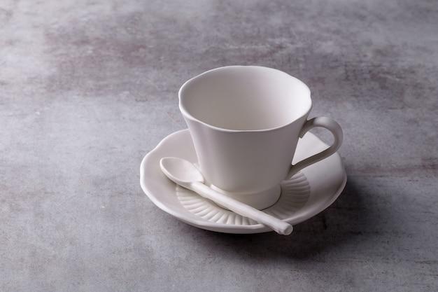 Сливочный чайник, чашка и блюдце на цементной доске