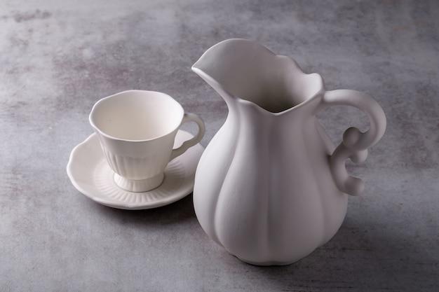 Сливочник чайника, чашка и блюдце на цементной доске