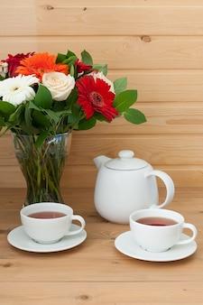 주전자, 컵 및 나무 테이블에 아름 다운 봄 꽃다발.