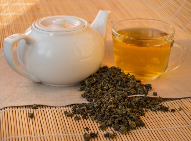 Teapot and cup of herbal green tea on bamboo napkin