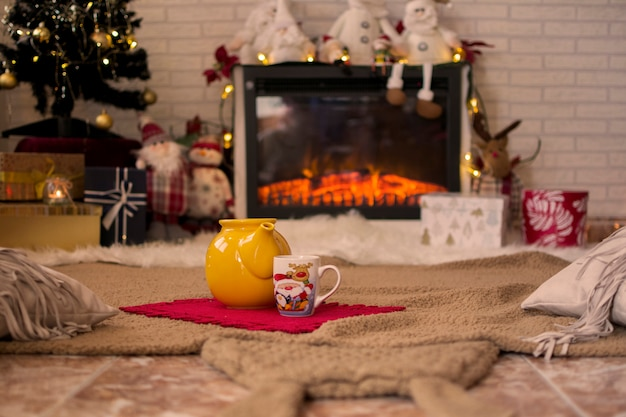 Teapot and cup of hot coffee, on the carpet surrounded by christmas decorations and lights.