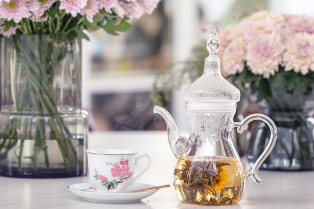 Teapot and cup with blooming tea flower and pink chrysanthemum flowers in glass vase on table.