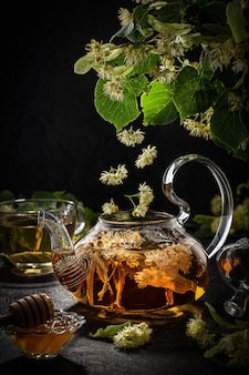 Teapot and cup with linden tea and flowers on a dark background