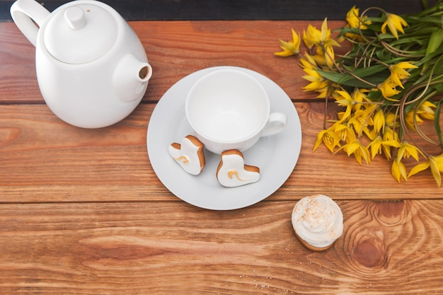 Teapot and cup with tulips on table. cupcakes top view, breakfast background. beautiful morning, tea party, celebration concept