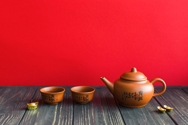 Teapot and cups on wooden tabletop