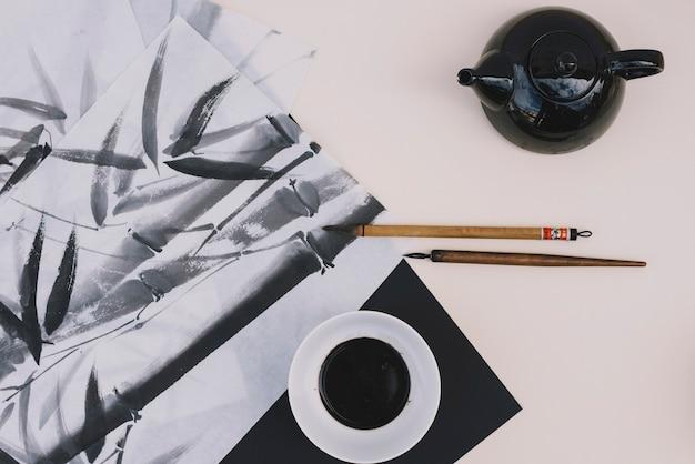 Teiera e inchiostro vicino al disegno di bambù
