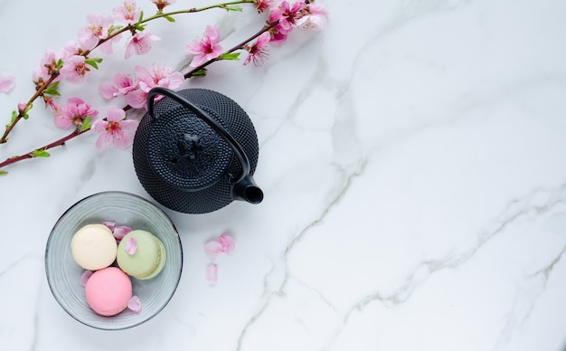 Teapot and macarons with flowers on marble background.