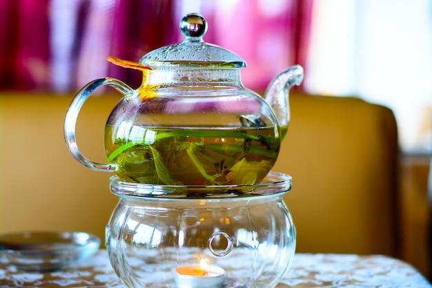 Чайник из травяного чая с апельсинами на деревянном столе