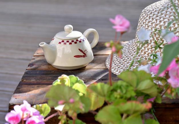 Чайник на деревянном столе на террасе с цветами и шляпой