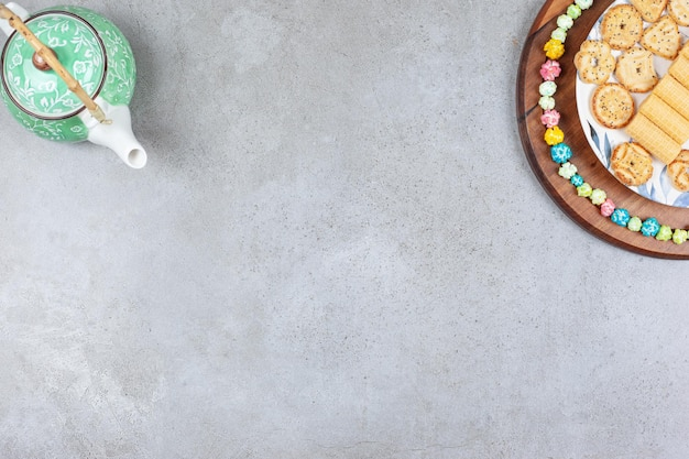 A teapot and a plate of assorted cookies ringed by candy on wooden board, on marble surface