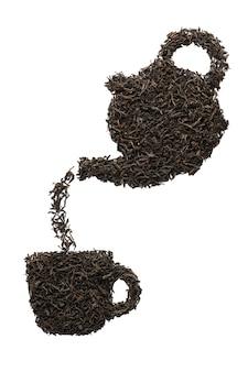 Чайник наливает чай в чашку. силуэт из сухих листьев черного чая. изолированный.