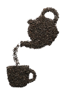 Teapot pouring tea into a cup. silhouette made of dry black tea leaves. isolated.