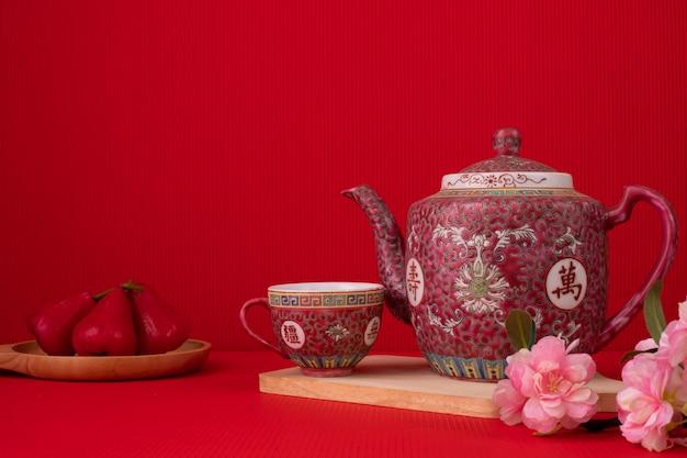 Teapot and sakura flower on red background,