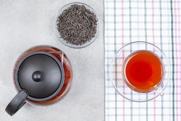 Una teiera e una piccola ciotola di foglie accanto a una tazza di tè su un asciugamano su sfondo di marmo. foto di alta qualità