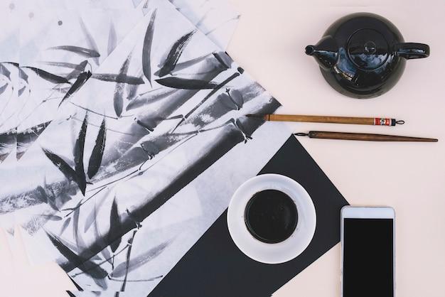 Teiera e smartphone vicino a foto di bambù