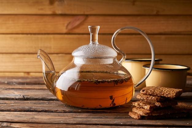 Чайник с заваренным горячим чаем и домашним печеньем на деревянном уютном фоне