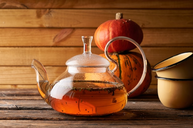Teapot with brewed hot tea ,pumpkin fnd cookies on a wooden, cozy background copy space