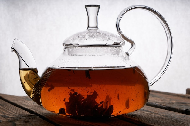 Teapot with brewed hot tea on a wooden, cozy background copy space