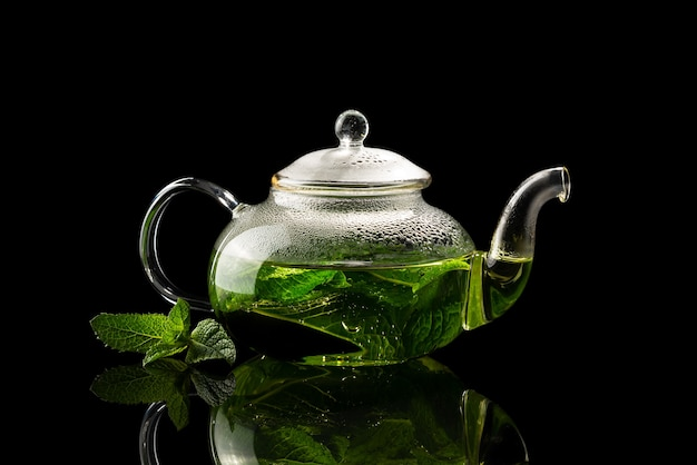 Teapot with brewed mint tea on a black background