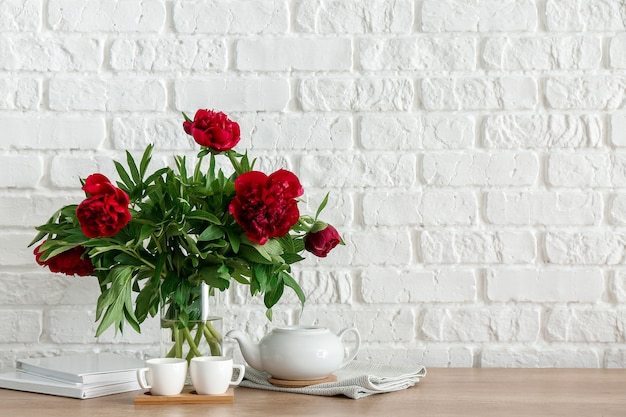 Teapot with cups and bouquet of flowers on kitchen counter