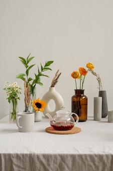 Чайник со свежим травяным чаем и кружка различных живых цветов в вазах, стоящих на столе на белой стене на кухне