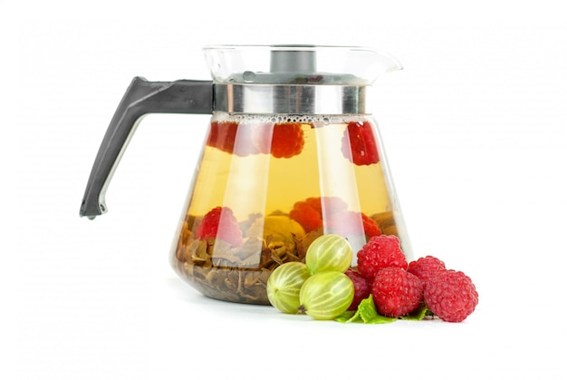 Teapot with fruit tea and berries on a white space