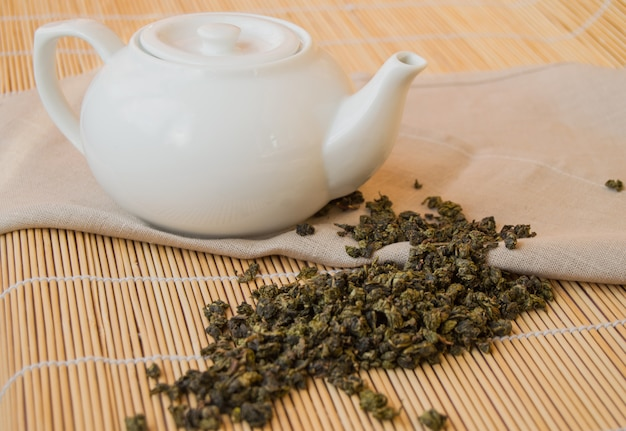 Teapot with green tea leaves on the napkin, bamboo background