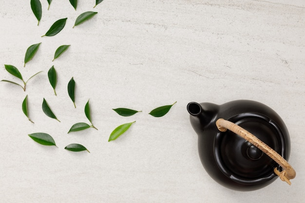 Teapot with organic green tea leaves on the white stone desk empty space creative flat lay