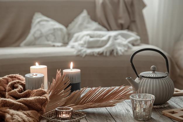 Чайник с чаем и свечами на столе в интерьере комнаты