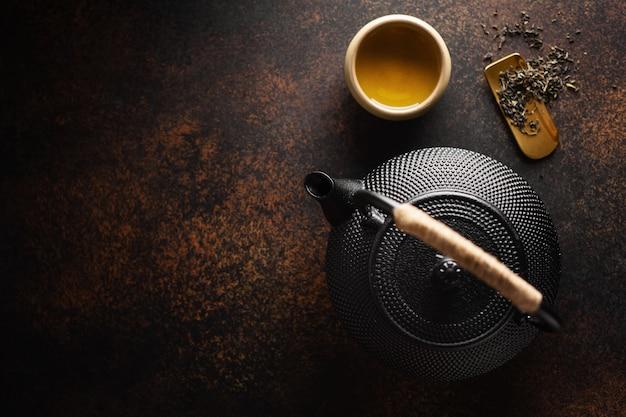 Teapot with tea on dark