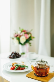 A teapot with tea on a dostochka on a table with plates and a bouquet of flowers on a blurred