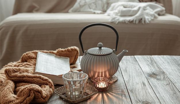 部屋の内部のテーブルにお茶、ニット製品、キャンドルが入ったティーポット。