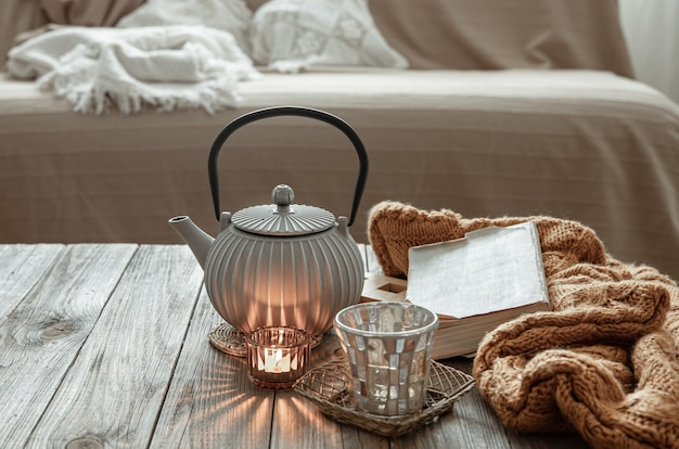 Teapot with tea, knitted item and candles on the table in the interior of the room