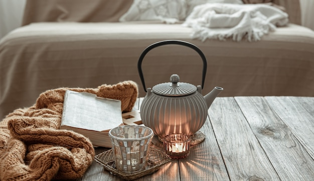 Teapot with tea, knitted item and candles on the table in the interior of the room.