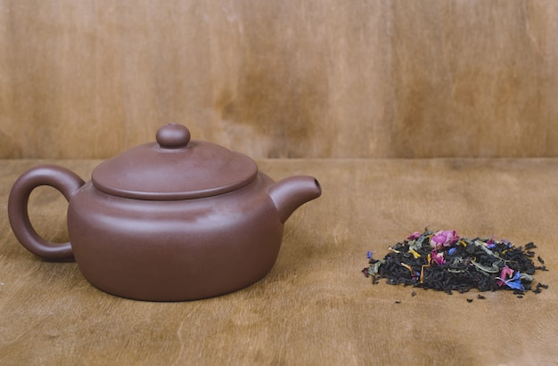 Teapot with tea and a pile of scented loose tea leaves and buds of dry flowers