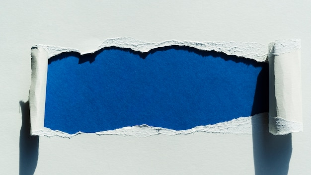 Tear in paper with blue color
