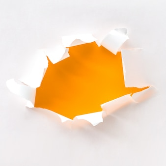 Teared paper hole in white paper over orange, square composition.