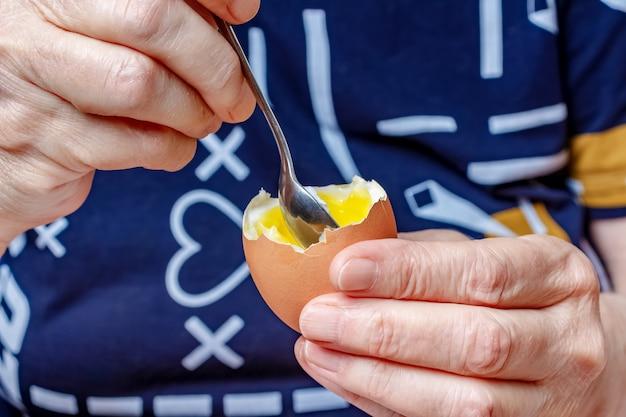 女性の手のクローズアップで液体卵黄と開いた鶏卵の小さじ