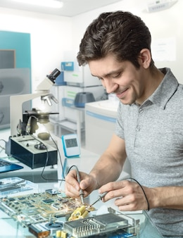 Tech or engineer repairs electronic equipment in research facility