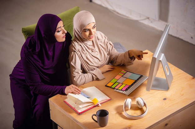 Tech happy and young two muslim women at home during lesson sitting in armchairs