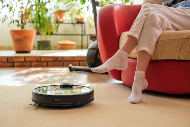 테크 하우스 청소, 로봇 진공 청소기 및 카펫 위의 여성 다리, 편안한 생활, 집에서
