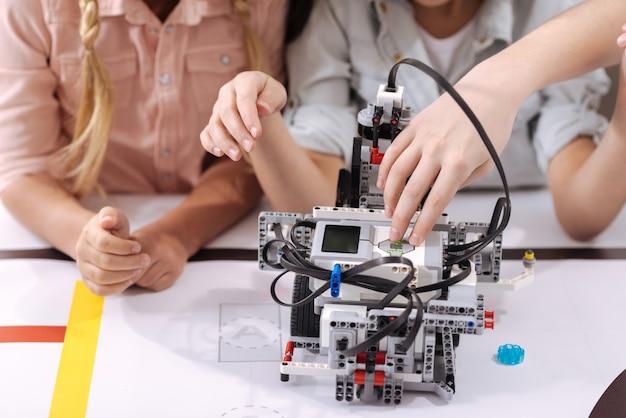 技術の進歩。学校に座ってロボットを構築しながら技術クラスを楽しんでいる熟練した有能な独創的な子供たち