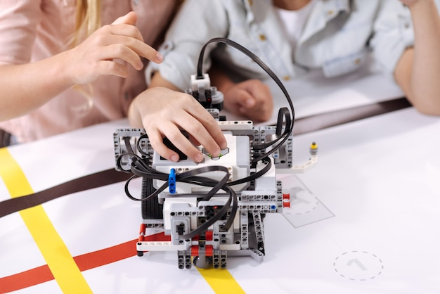 Tech research . talented capable involved kids sitting at school and enjoying class while constructing robot