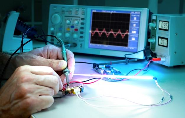 Tech тестирует электронное оборудование в сервисном центре