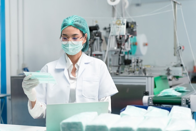 Technical asian woman checking quality and clean of mask for preventing coronavirus at factory