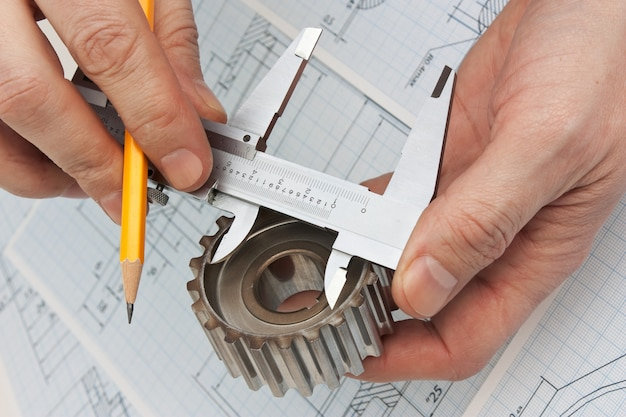 Technical drawing and tools in hand