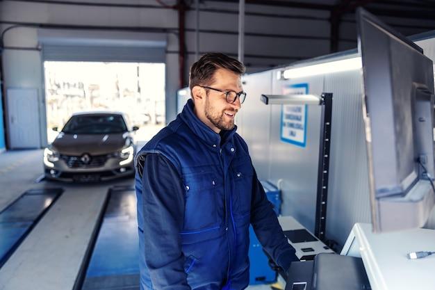 자동차의 기술 검사. 기술 검사, 자동차 전자 장치에 대한 자동차 진단. 파란색 유니폼을 입은 남자가 컴퓨터 앞에 서서 화면보기 매개 변수를 조정합니다.